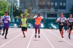 5 runners race toward the finish line and straight toward the camera  on an outdoor track.