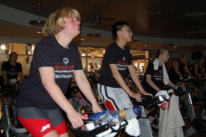 Three Special Olympics athletes train on stationary bikes in a gym.